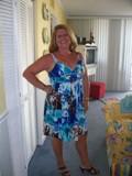 Sylvia Fountain indoors in a blue flowery sundress
